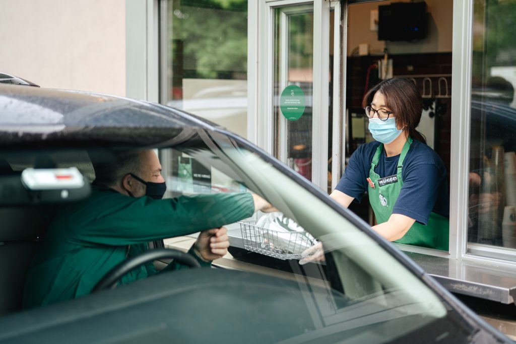 A Starbucks employees gives an order to a customer in the drive-thru.