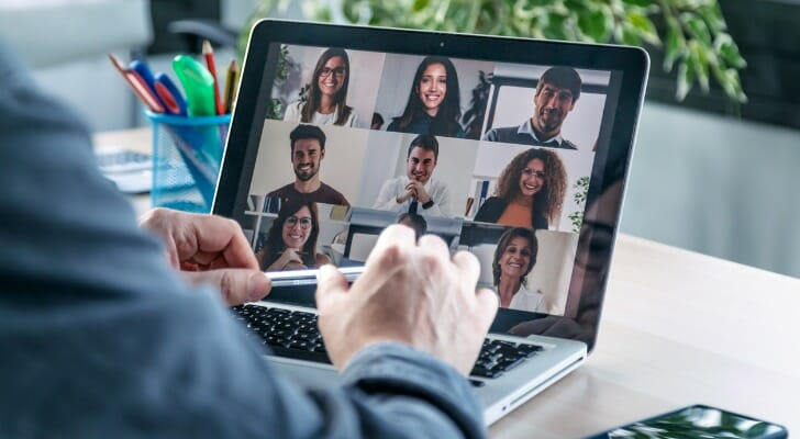 Image shows a person's hands at the keyboard of their laptop; their laptop screen shows a grid of faces in a video conference call. SmartAsset analyzed data to find the best cities to work from home in 2021.