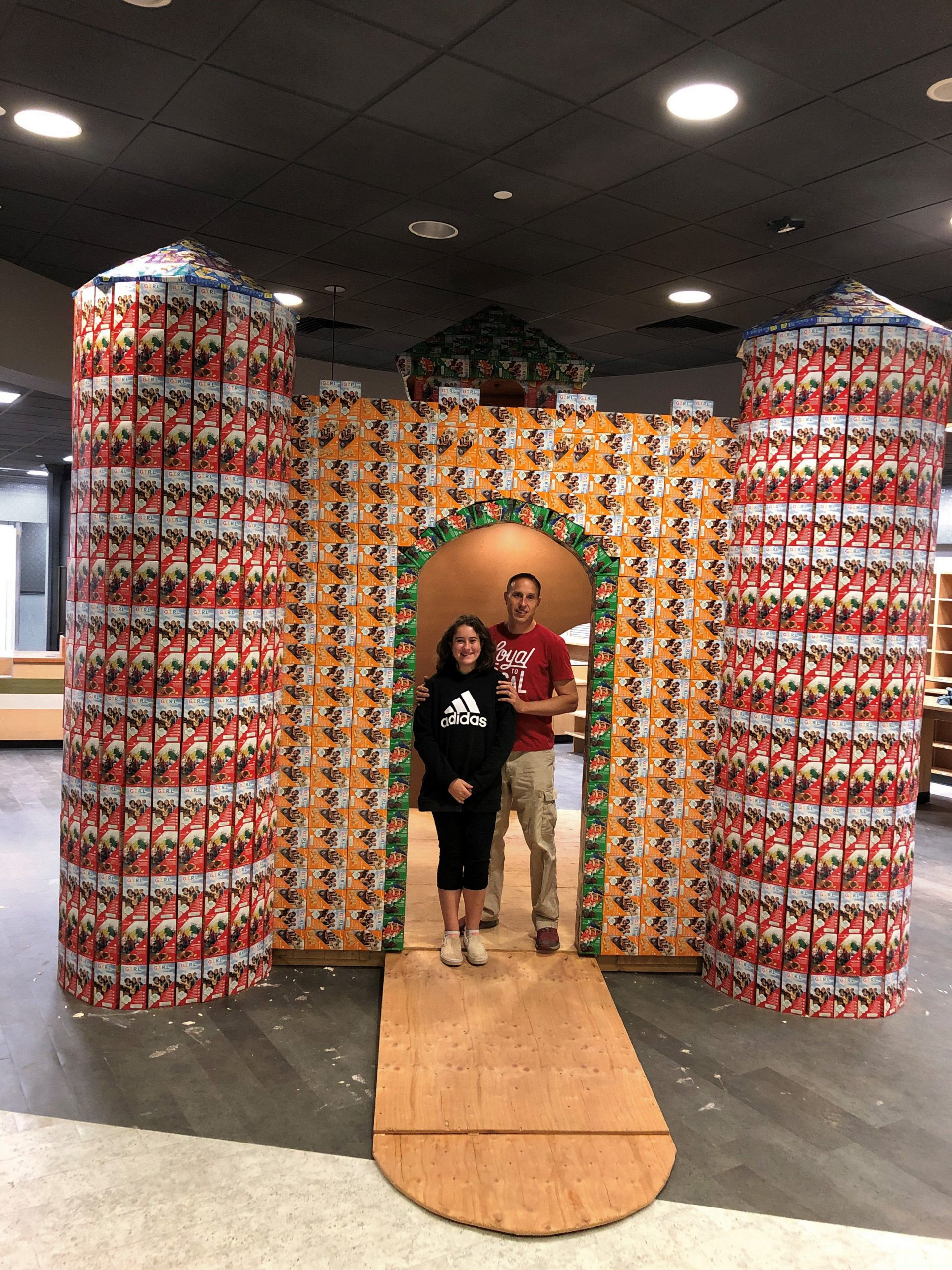 Girl Scout Mija with her father in front of the cookie castle
