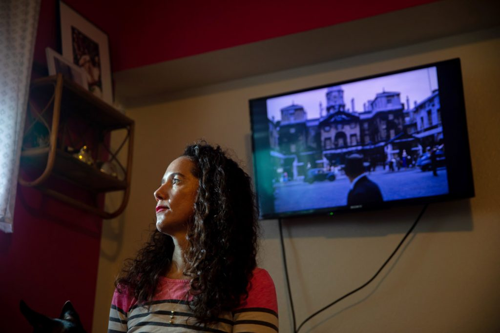 A woman looks off into the distance toward a window with an old photograph on a television screen behind her.